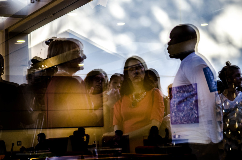 Reflected in the window of the  Hub grill at Claremont McKenna College, Dean of Students Mary Spellman, left, takes questions from students as she faces calls to resign over a lack of action against racist incidents on campus.