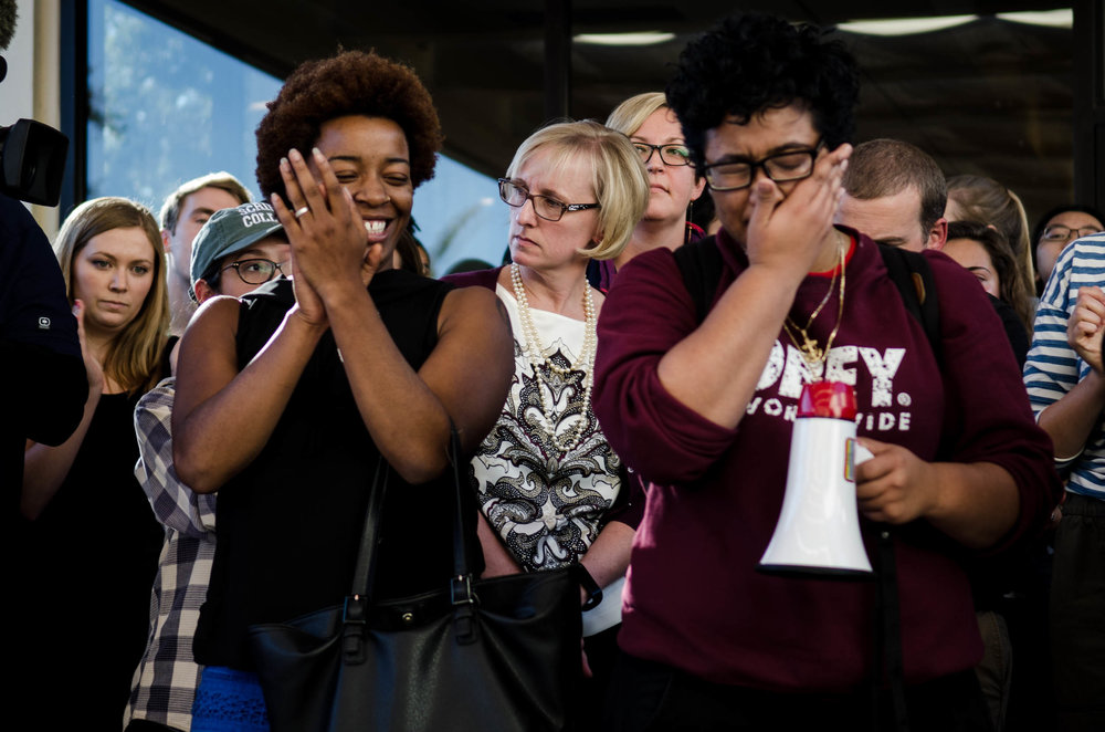 Claremont McKenna College Dean of Students Mary Spellman, center, reacts to calls for her resignation at a demonstration on Nov. 11, 2015.