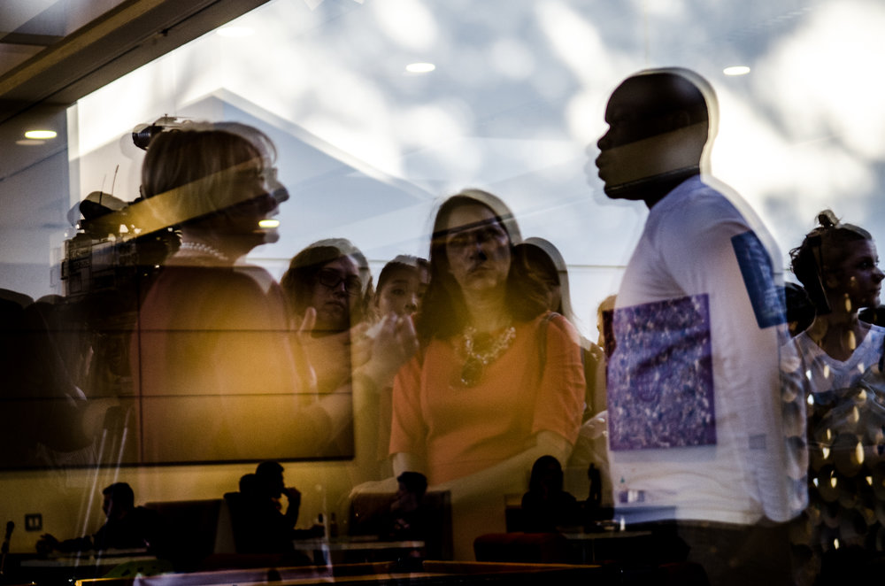 Reflected in the window of the Hub grill at Claremont McKenna College, Dean of Students Mary Spellman, left, takes questions from students in Nov. 2015 as she faces calls to resign over a lack of action against racist incidents on campus.
