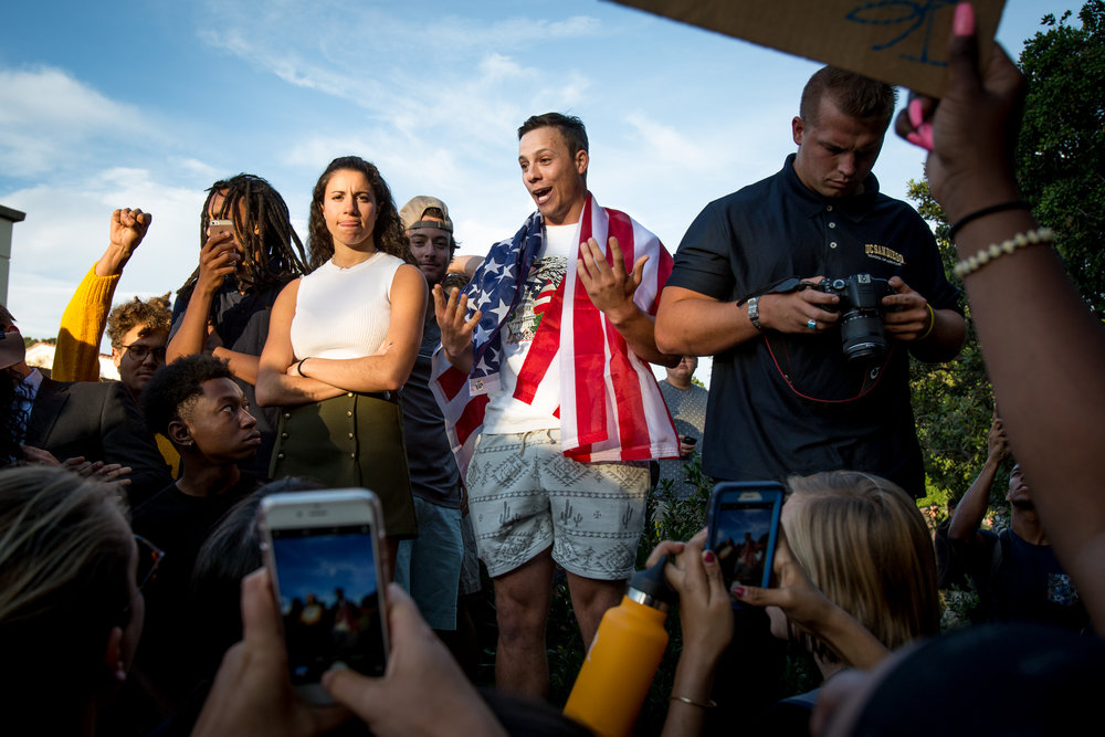 """""""That's not how free speech works,"""" yells junior Chase Eller, draped in an American flag, while surrounded by about 300 students chanting """"Black lives, they matter here"""" during a blockade of a speech by conservative writer Heather Mac Donald at Claremont McKenna College on April 6, 2017."""