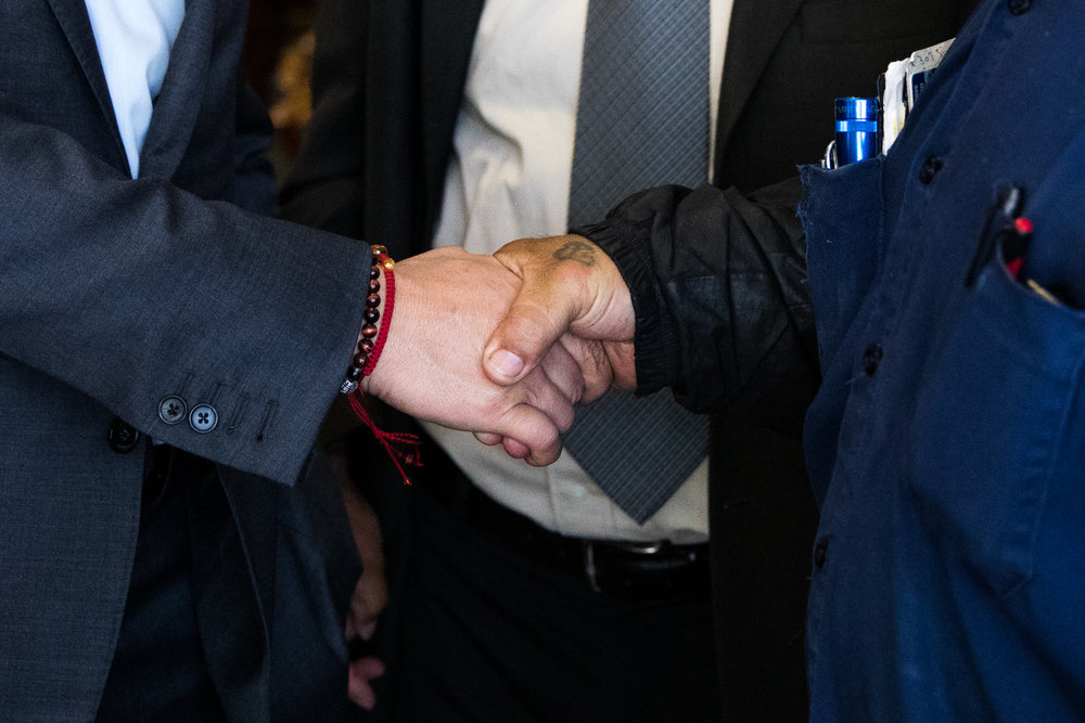 U.S. Senate candidate Kevin de León, left, shakes hands with Dominic Salcido, a maintenance mechanic at Pitzer College, in April 2018.