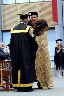 Lachlan graduating from Macquarie University. He is wearing a Possum Cloak which is a traditional Wiradjuri garment.