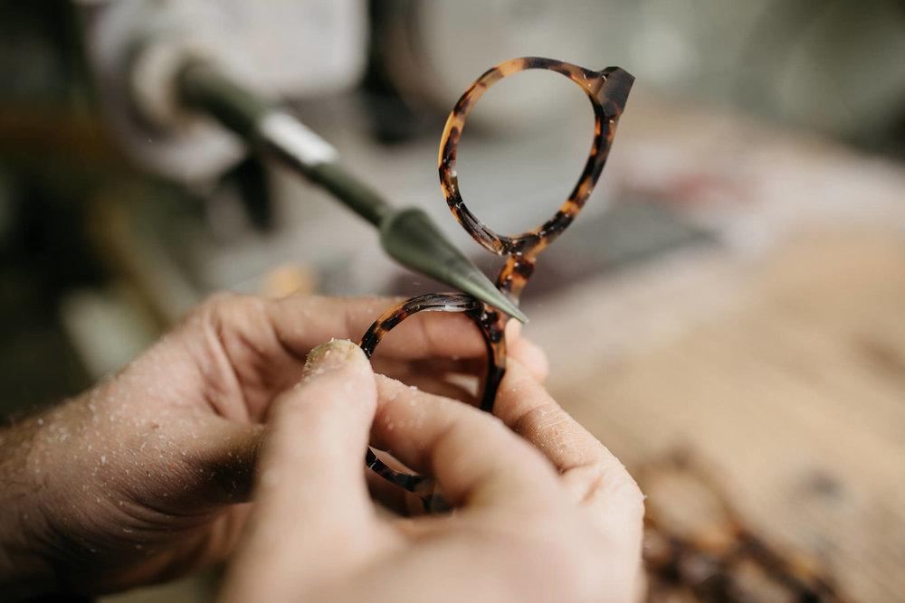 """Notre atelier : un fil entre générations - La dernière école de lunetterie d'Oyonnax a fermé il y a plus de 35 ans. Aujourd'hui, le savoir-faire se transmet de génération en générationau sein même de notre atelier.Ici, notre artisan utilise une """"machine à canneler"""" qui permet de poncer avec minutie les plaquettes – la partie en contact avec le nez.Un savoir-faire de précisionqui lui a été transmis il y a une vingtaine d'années par son maître d'apprentissage. Et qu'ils sont désormais 3 seulement à maîtriser à Oyonnax."""