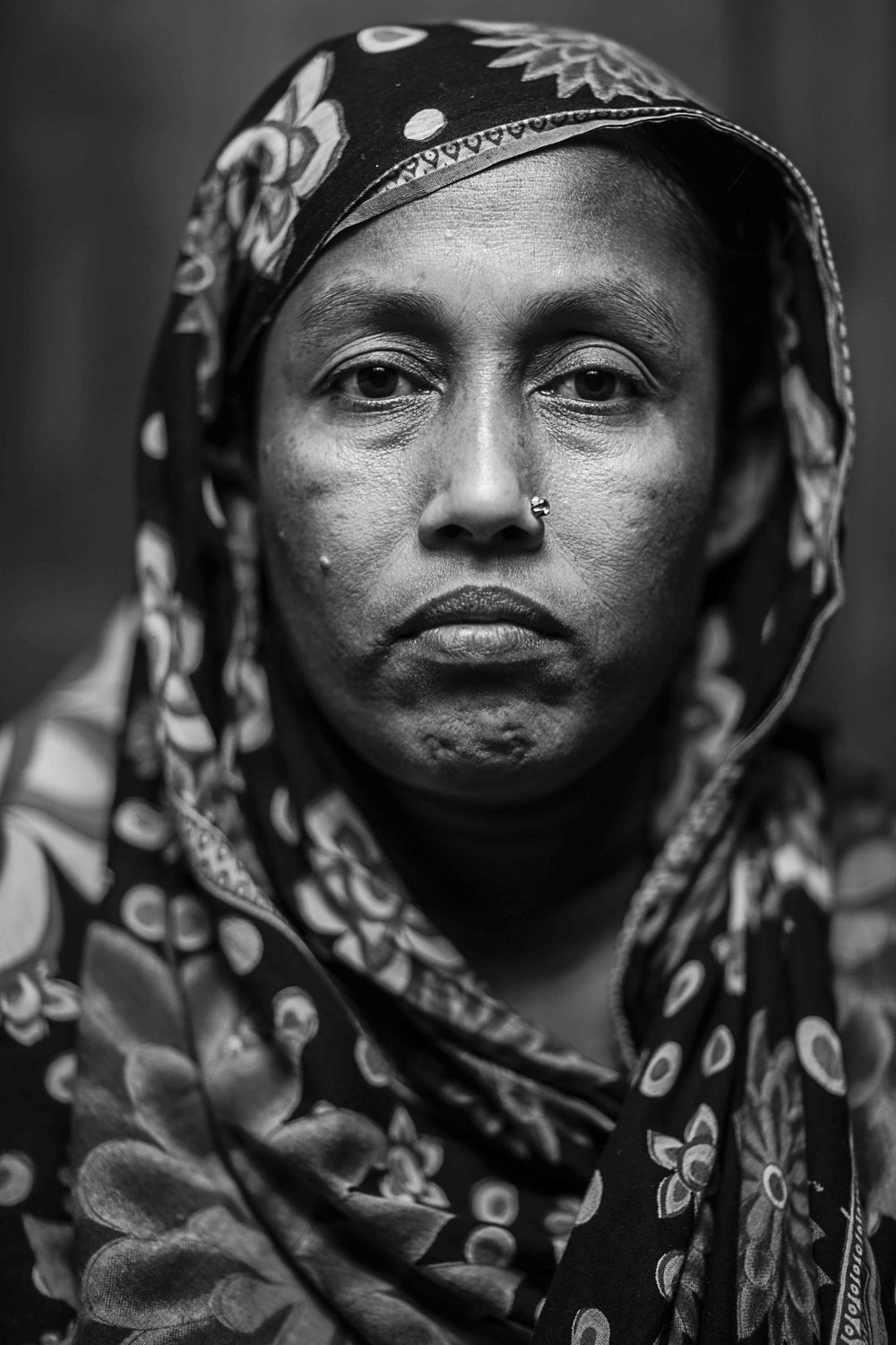 Nasima Begum, wife of Rubel, has been beside her husband's bed since November. They have two young sons in Comilla and are finding it hard to support their family.
