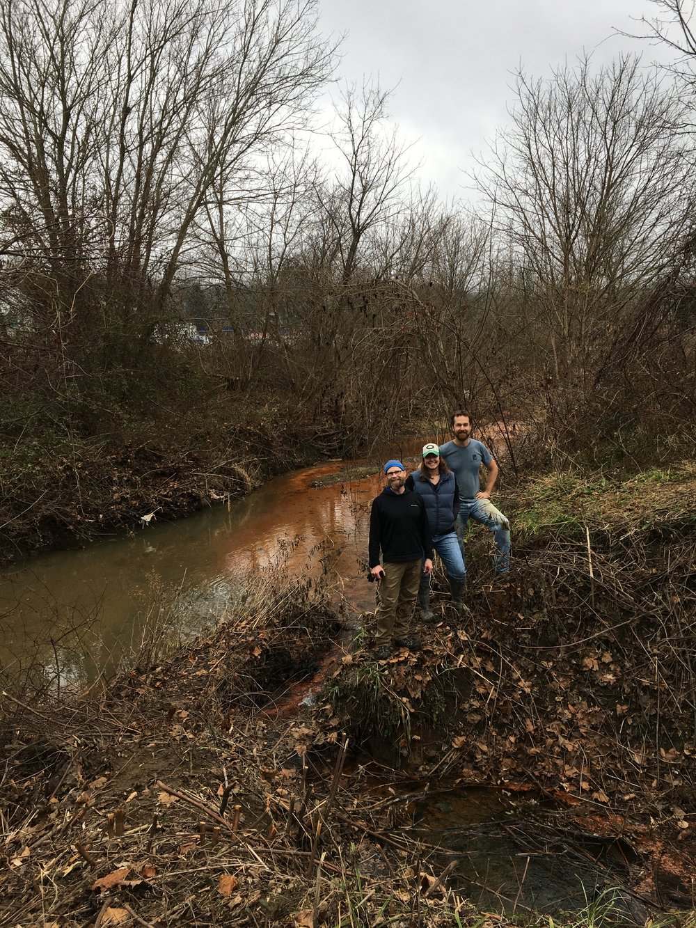 Guy Riefler, Michelle Shively and me posing next to the acid mine seep at Corning OH, this day we cleared the area of thorny bushes. This seep leeches over a million gallons of pollution into Sunday Creek everyday.