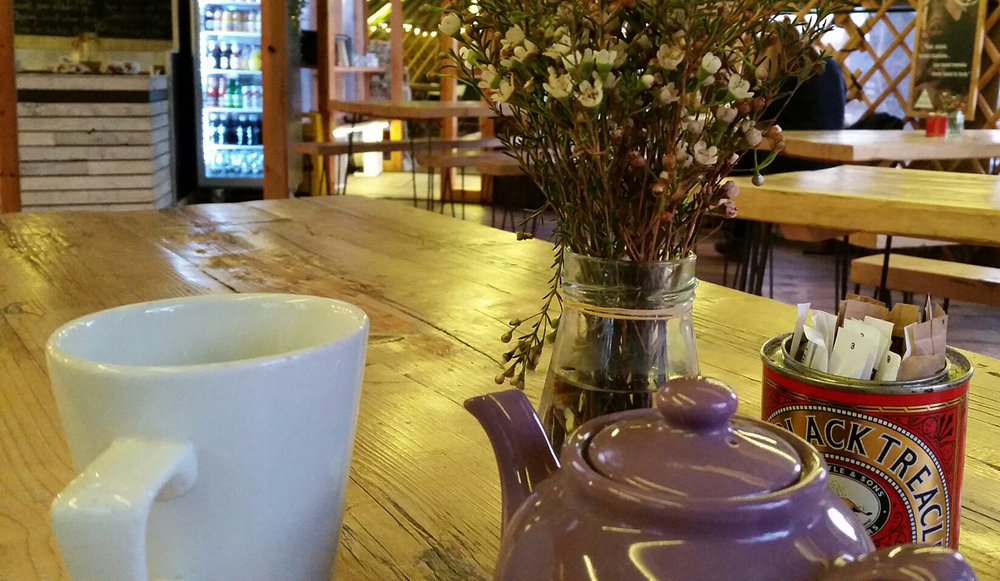 Teapot, cup and flowers on a cafe table.