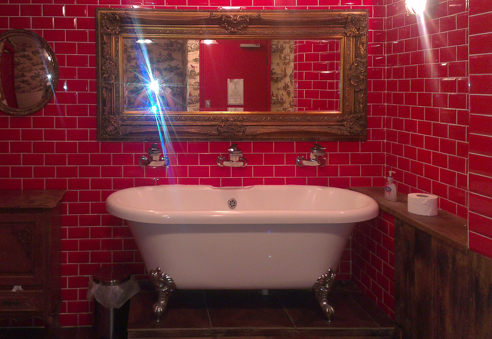 Claw-footed bathtub with three taps in Wembley pub. © Tamzin Doggart.