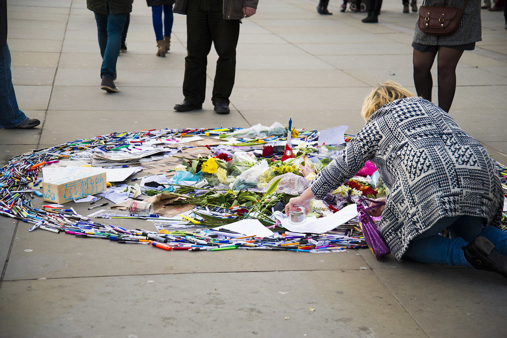 A woman giving condolences to the victims of the Charlie Hebdo shootings in Paris, Trafalgar Square, London