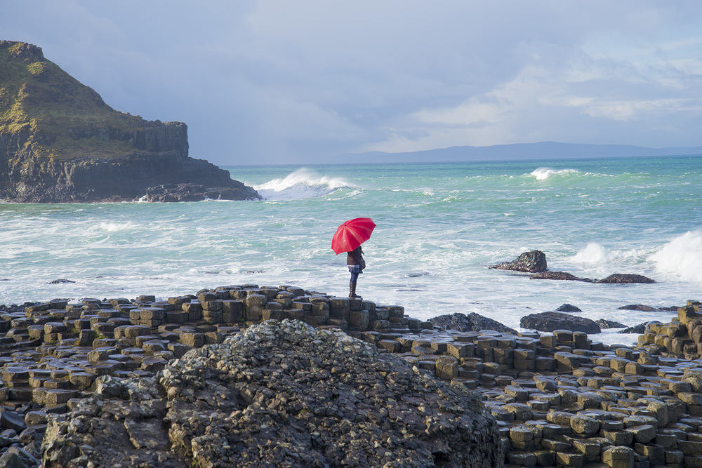 A woman and her umbrella on the Causeway Coast, Northern Ireland