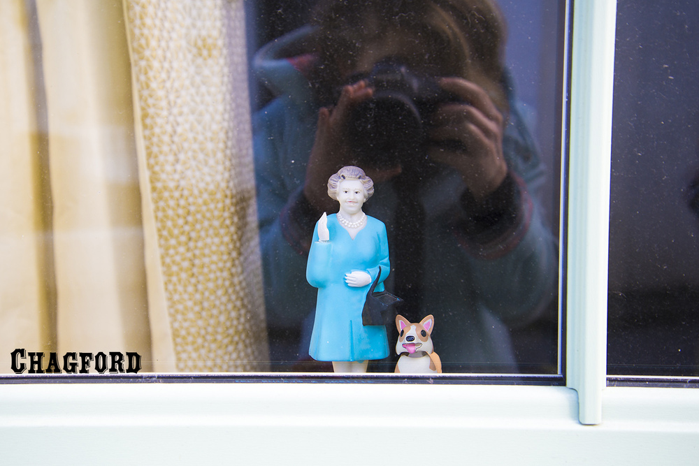 Queen of England bobblehead in home window, Chagford, Devon, UK