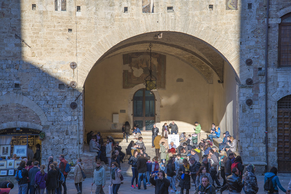 An archway where families are gathered in the sun, San Gimignano, Tuscany