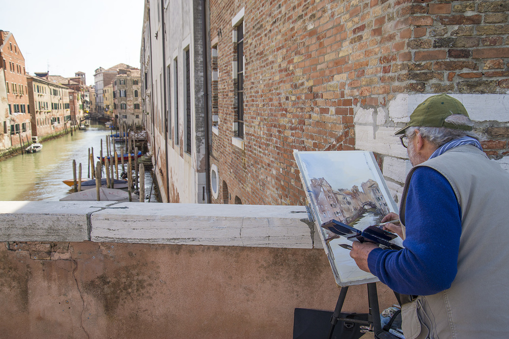 An artist painting alongside one of the smaller canals, Venezia, Italia