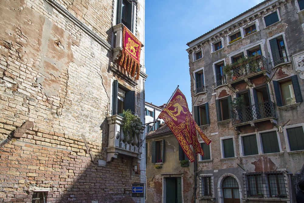 A corner apartment with two flags with the colors and symbols of Venezia, Italia