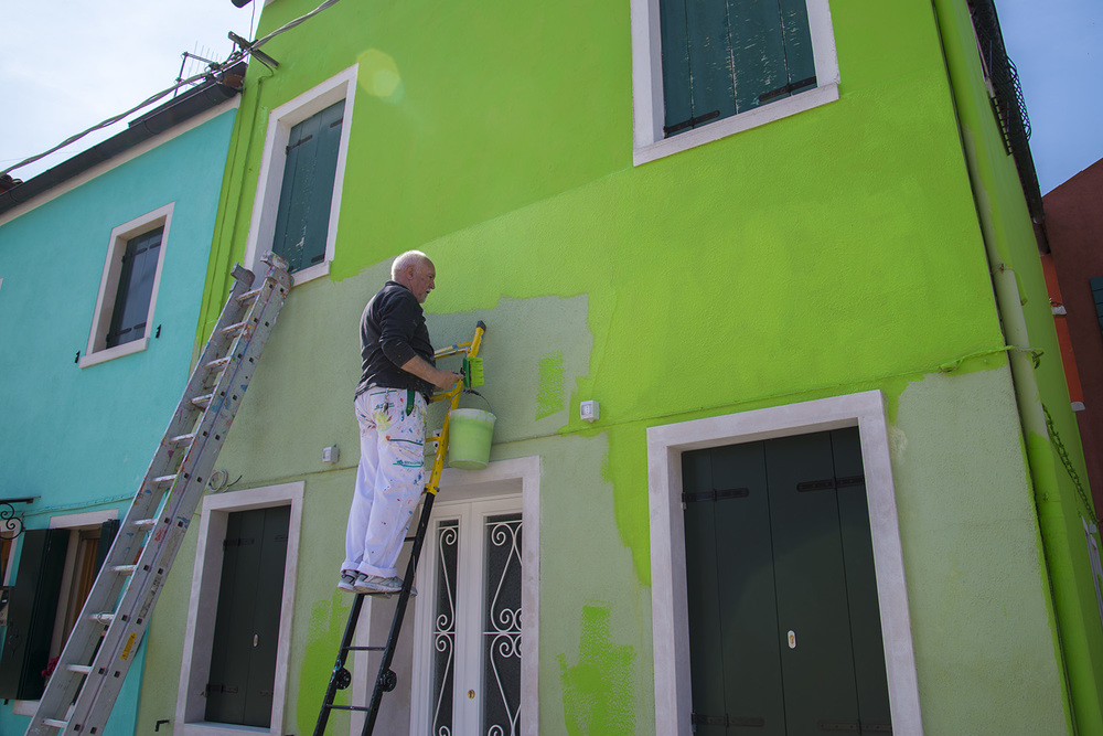 A painter touching up the outside of a house in Burano, Italia