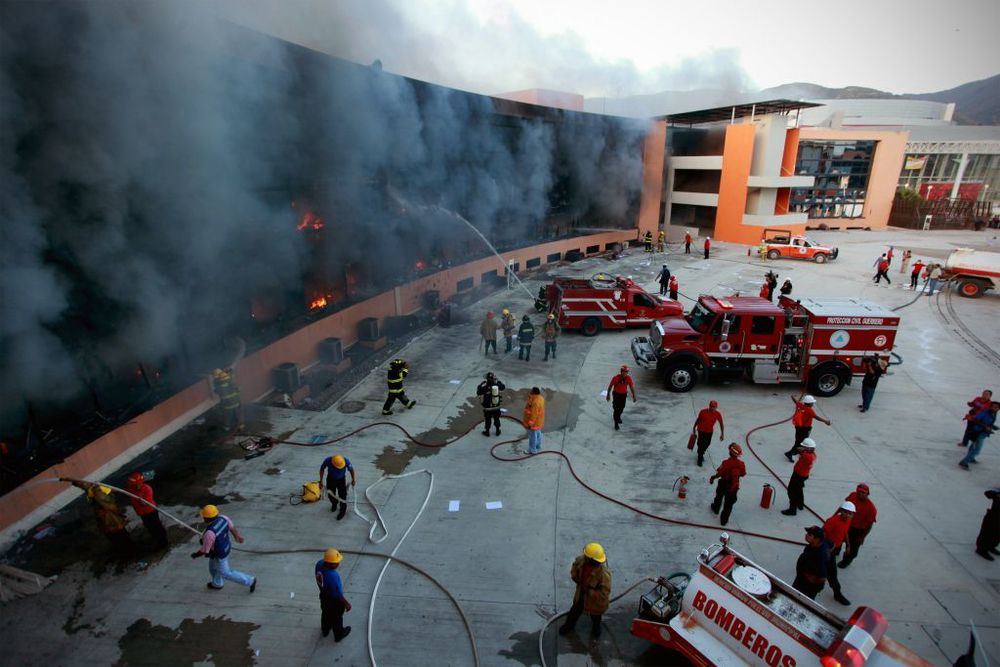 Protestors in Acapulco, Mexico set fire to a state capital building in response to the disappearance of 43 teachers linked to local drug cartels. Photo courtesy of Felix Marquez/AP.