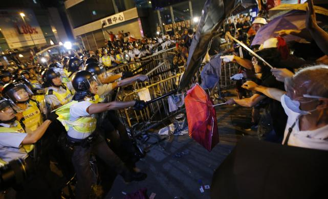 Police with riot shields warn pro-democracy protestors in Mongkok, Hong Kong, at a rally. REUTERS/Carlos Barria