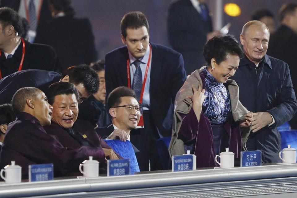 Vladmir Putin wraps shawl around Xi Jinping's wife Peng Liyuan as Xi chats with Obama at APEC summit, causing media frenzy. Source: AP.