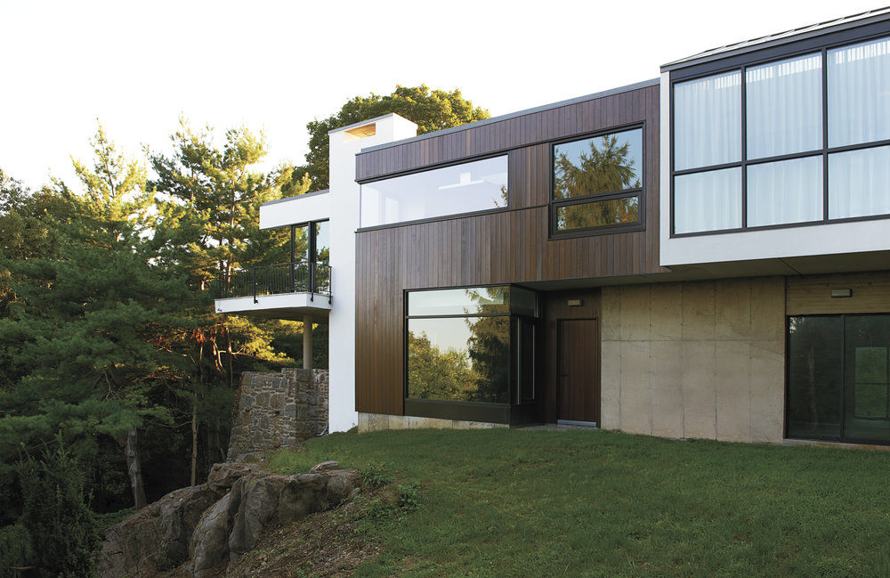 wood and stone siding large glass windows