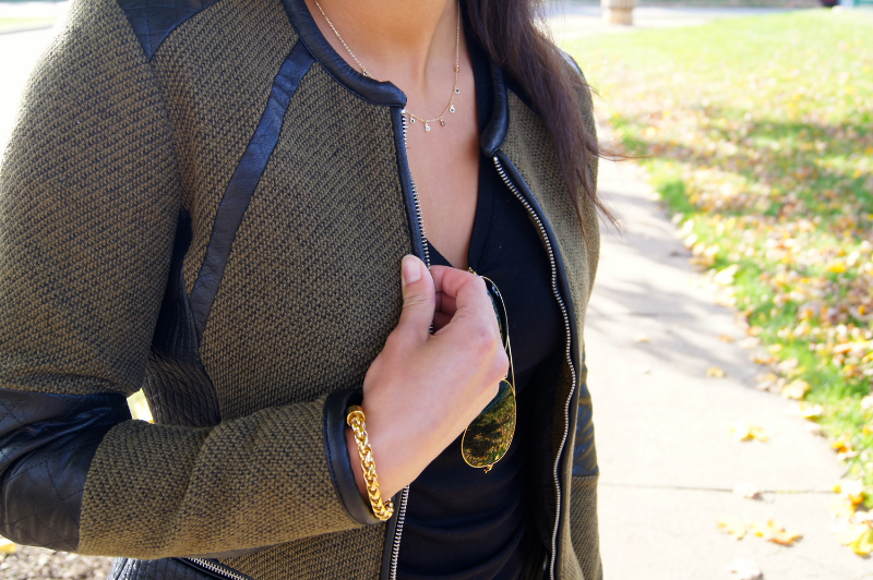 This detail shot shows the quality material of this jacket. Besides the leather, the green fabric has a rich warm tone to it, which is why the gold accessories are a great compliment to it (including the sunglasses frame).