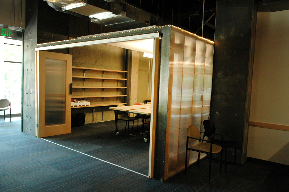 Largest meeting room available seats about 20 people with accordion polycarbonate in wood frame doors.
