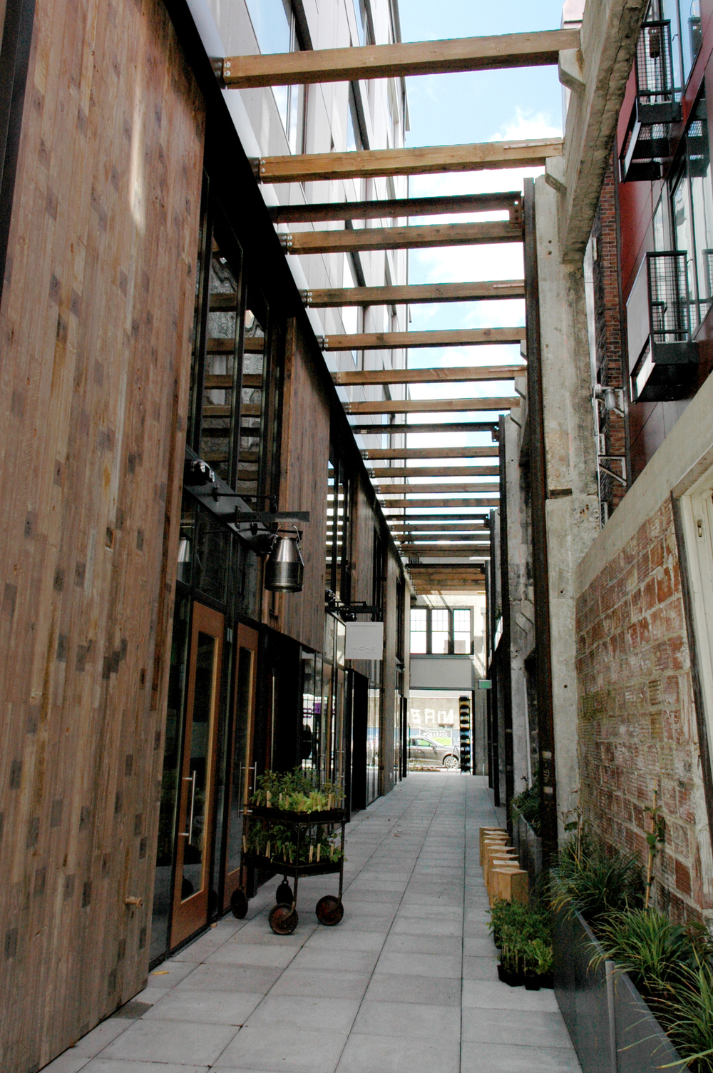 "Chophouse Row mews - an alleyway ""carved"" into the Chophouse building - an old, one-story autorow ""relic."" The concrete frame and clay tile are left, and the wood decking is used as cladding for the new building."
