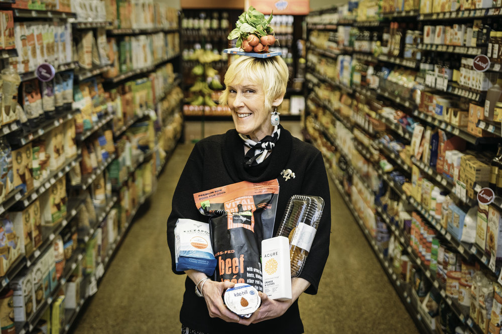 """Annie shows off some of her favorite products at the co-op.""""I live to laugh, I am loyal and I love my co-op,"""" she says."""