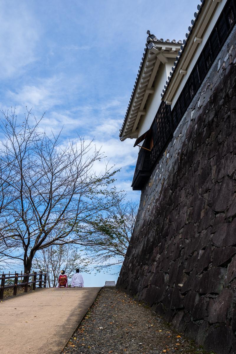 運氣好剛好遇見兩位日本新人著傳統禮服拍婚紗,我躲在後面下坡處避開攝影師把我入鏡。新人與熊本城高聳圍牆相呼應,整個給它古色又古香!