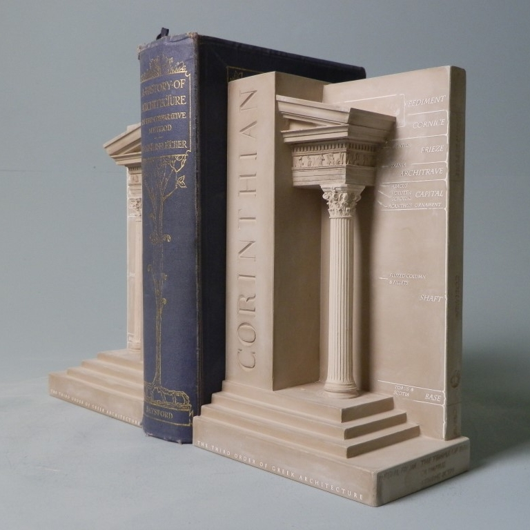 Corinthian Order Bookend Set £60.00 / RRP £150.00 (Height 23cm) The Third Order of Greek Architecture These Timothy Richards bookends of the the Third Order of Greek Architecture would make a beautiful display in any study or office, on bookshelves or windowsills alike. They would be a striking gift for any student or profession architect looking for a place to keep their many books. The Corinthian order was adopted by the Romans from the Greeks and was bestowed with the association of beauty and love. It is the most popular of the Greek Orders. Detail has been taken from the Temple of Zeus Olympia, Athena, BC 174. The temple was built from designs by Cossutius, a Roman architect. This temple was important as parts of it were taken to Rome where its presence resulted in many copies and the popularising of the Corinthian order.