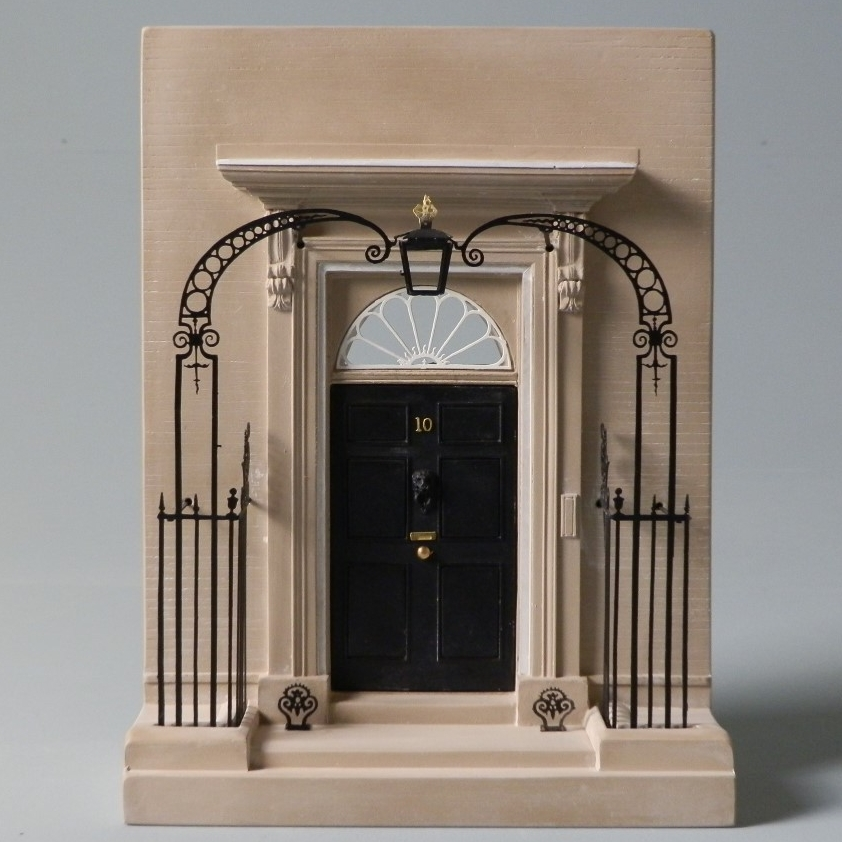 "Built by Sir George Downing When – 1680's Where – London, England This detailed scale Timothy Richards doorway model of one of London's most iconic political entranceways would make a stunning statement piece for any mantelpiece, bookshelf or display cabinet. The official residence of the British Prime minister in Westminster, London. No.10 Downing Street is possibly the most photographed and famous front door of any politician in the western world. The building is over 300 years old and contains around 100 rooms. The land on which Downing Street stands was originally bought in 1654 by Sir George Downing; the notorious spy for Oliver Cromwell. He intended that town-houses on this street be built ""for persons of good quality to inhabit…"". In 1732, three buildings were offered to Sir Robert Walpole who commissioned William Kent to join them together to become No.10 Downing Street."