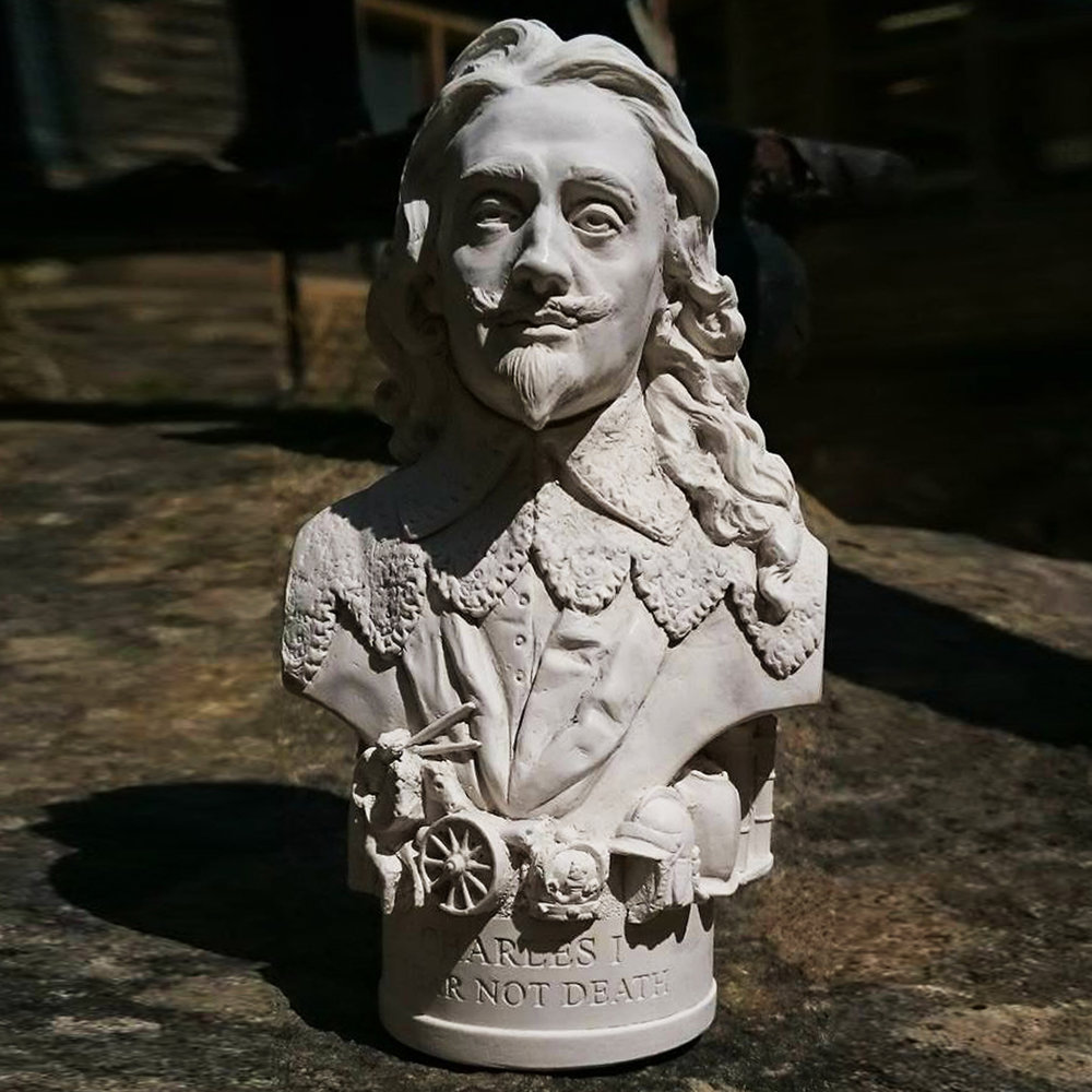 "Bust of Charles I made in British Gypsum Plaster.  Charles I was the first of our monarchs to be put on trial for treason and it led to his execution. This event is one of the most famous in Stuart England's history – and one of the most controversial. The Bust Based on illustrations and photographs of King Charles I, this sculpture was crafted at our studios in Bath and makes a truly regal addition to the mantel, bookshelves or occasional table for any 'royalist'. Around the base. For this bust we have included a crown, helmet and breastplate, canon, charging horses and soldiers going to war. The etch around the base reads -  ""I FEAR NOT DEATH"""