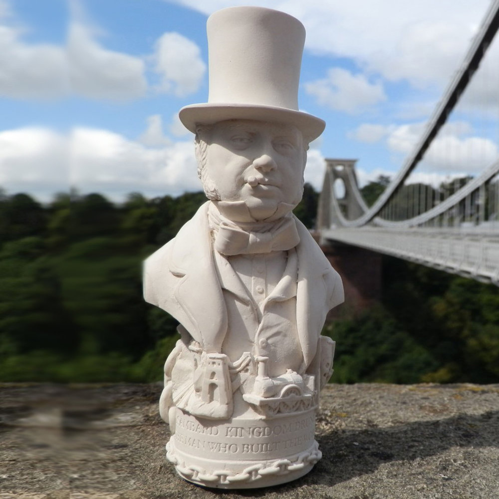 "Bust of Isambard Kingdom Brunel made in British Gypsum Plaster. Brunel remains the most famous engineer in history; famed for his bridges and dockyards, tunnels, steam ships and Great Western Railway. As with all Famous Faces there are objects around the base. For this bust we have included some of the great engineers master pieces including the Box Tunnel; Clifton Suspension Bridge, A Steam Locomotive and the bow of the SS Great Britain. The etch around the base reads - ""THE MAN WHO BUILT THE WORLD"""