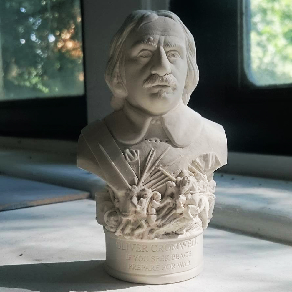 """Bust of Oliver Cromwell made in British Gypsum Plaster. From fen farmer, to puritan and Lord Protector. Cromwell fought for freedom against Charles I's catholic ideas, financial excess and notion of 'rule by divine right'. As one of history's most controversial figures he has been referred to as both military dictator and hero of liberty. (1599-1658) As with all Famous Faces there are objects around the base. For this bust we have included the chopping block, round head breastplate, drum, crown, helmet and charging horses and soldiers going to war. The etch around the base reads - """"IF YOU SEEK PEACE, PREPARE FOR WAR"""""""