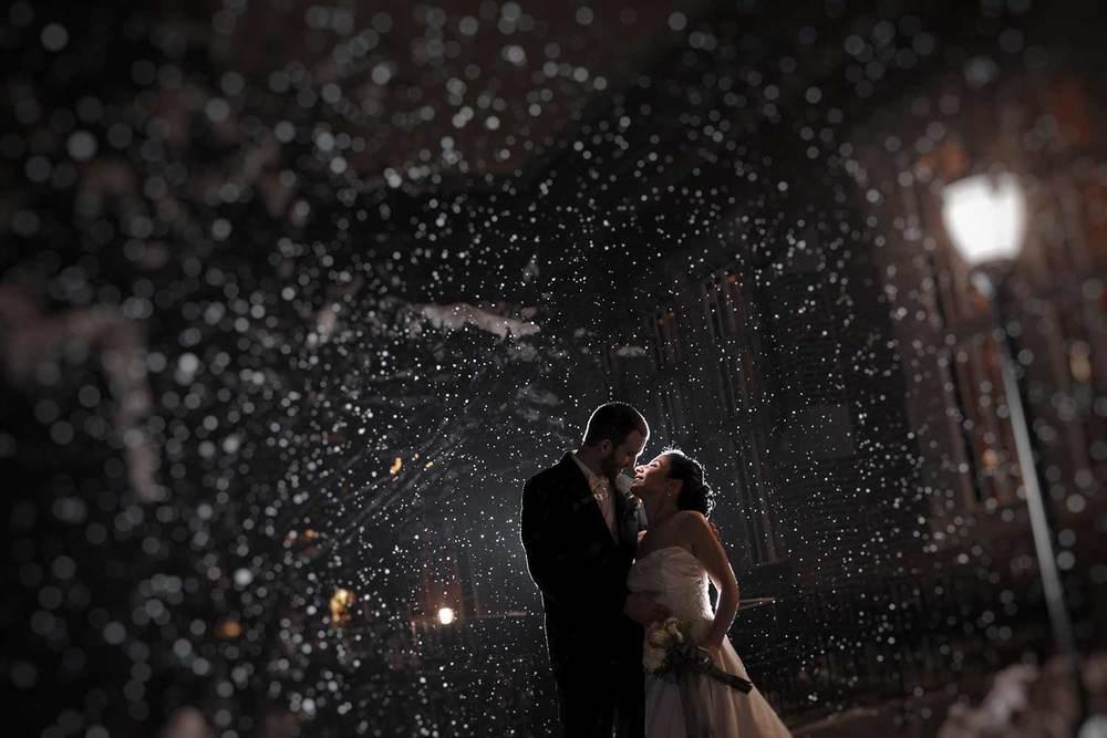 perfect snowfall for a winter wedding kiss outside Alden Castle in Brookline, Massachusetts