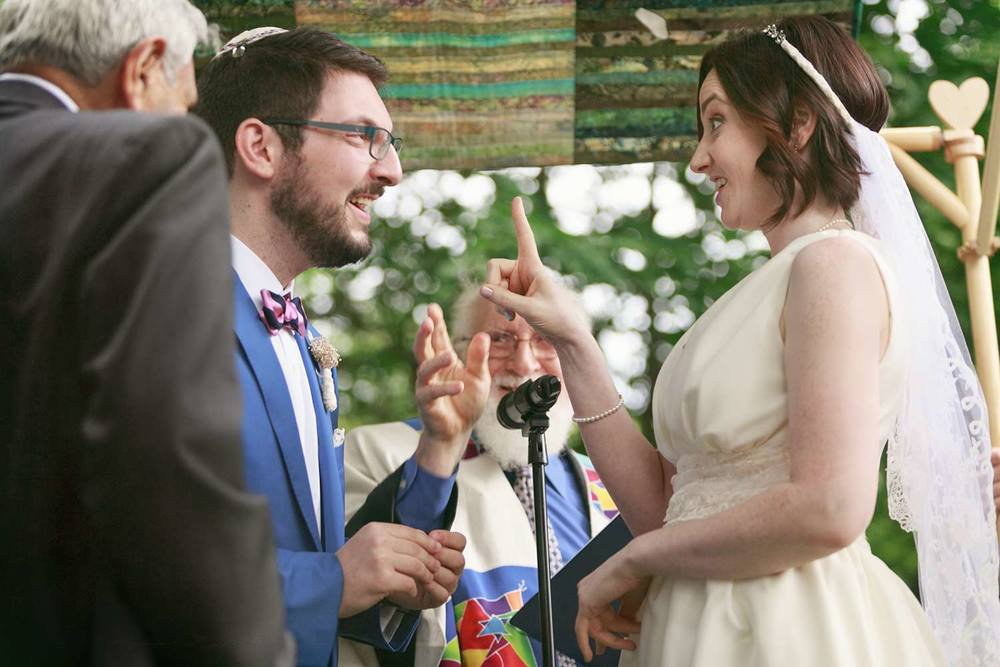 under the handmade chuppah and ready for the ring at a backyard jewish ceremony in Lexington, Massachusetts