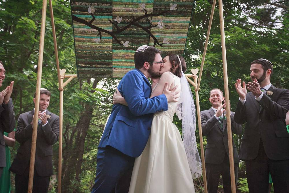 big kiss under the quilted chuppah