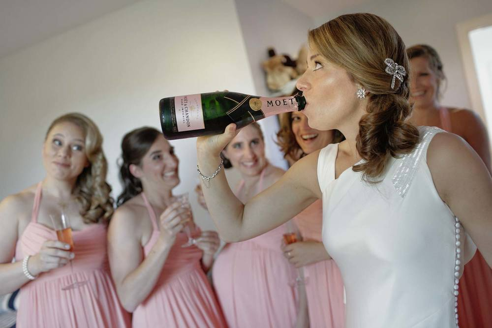 taking a swig of pink champagne with the bridesmaids before the garden wedding ceremony