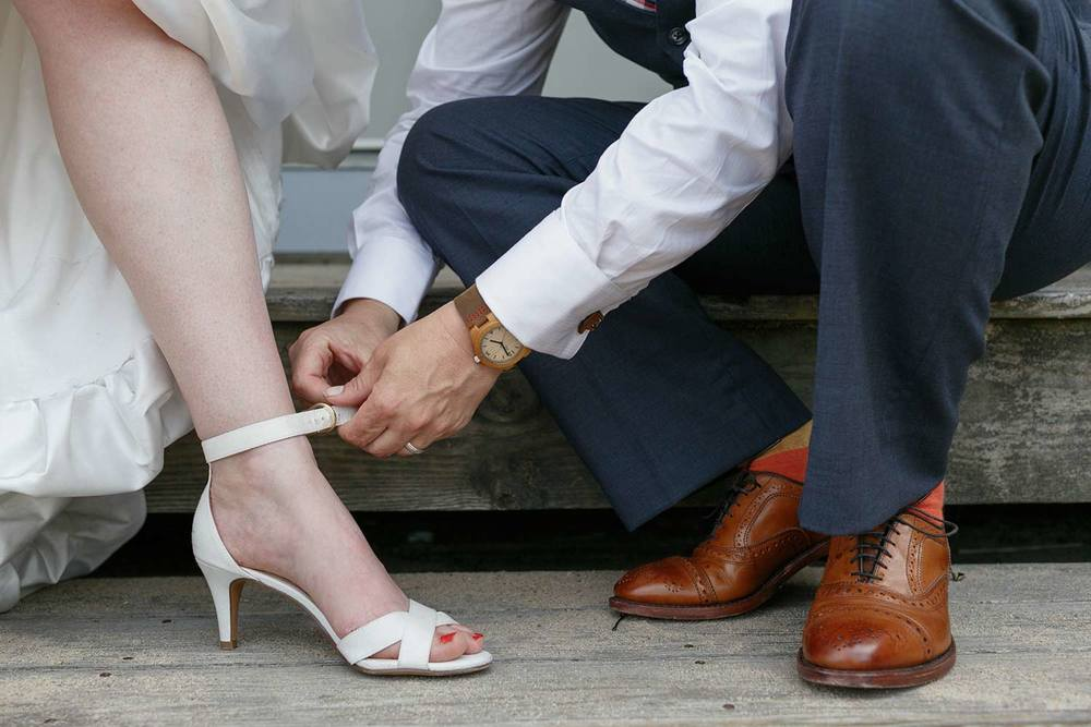 fixing the bride's ankle strap, Provincetown wedding
