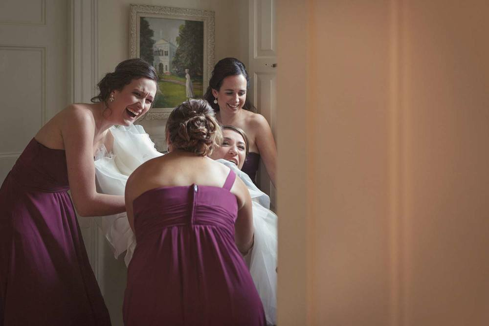 bride laughing getting into tulle dress with bridesmaids at glen magna farms wedding