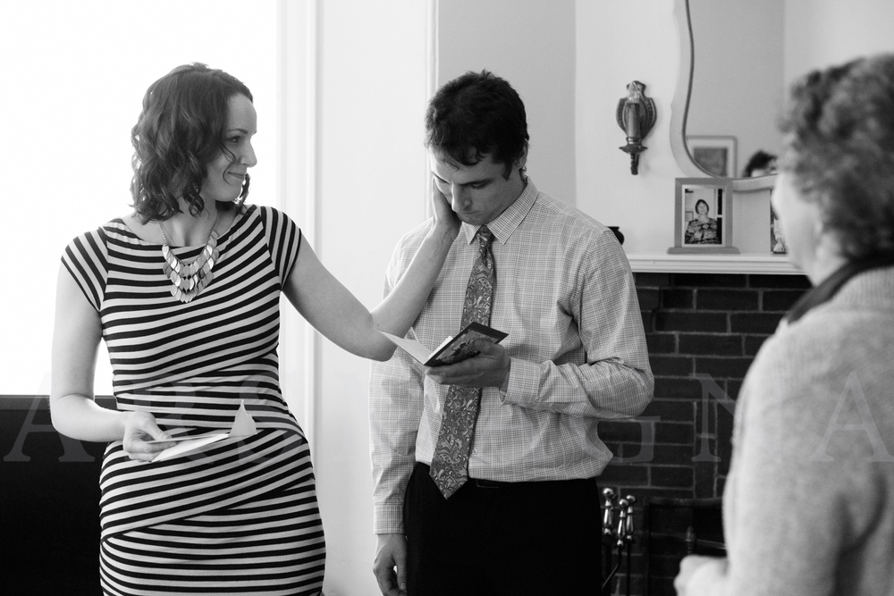 This is one of my favorite images from their wedding day. A gentle gesture of caring from wife to husband, as he receives and reads a card from his aunt. A portrait of the groom's mother, who passed away, is on the mantle figuratively and literally watching over him on his wedding day.