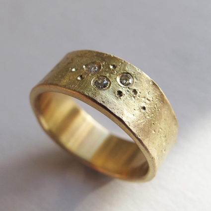 Recycled gold textured ring set with scattered diamonds.