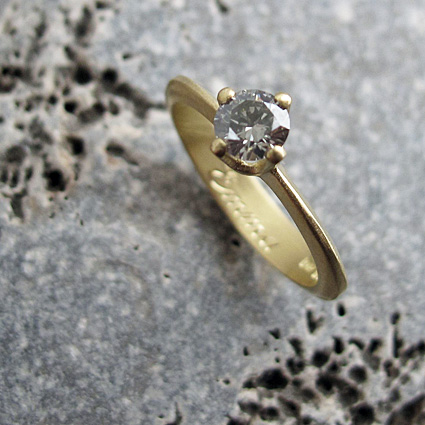 0.25 carat grey diamond and 18 carat yellow gold engagement ring with hand engraving.