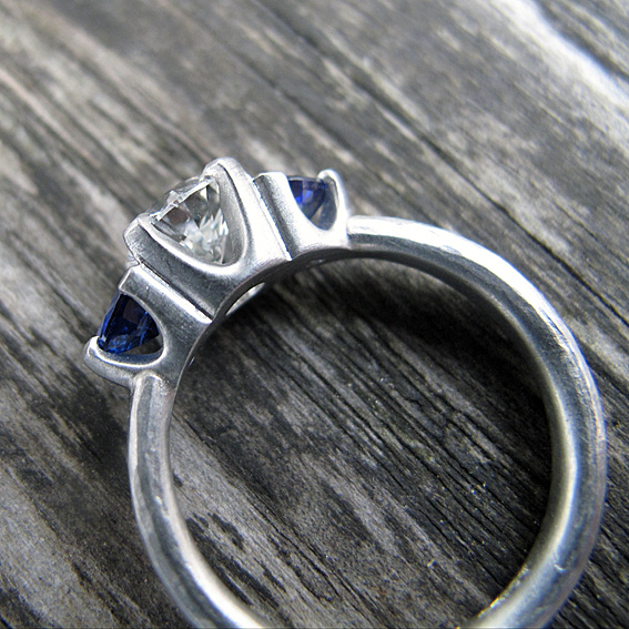 0.5 carat diamond, trillion blue sapphires and platinum engagement ring with an organic, hammered finish.