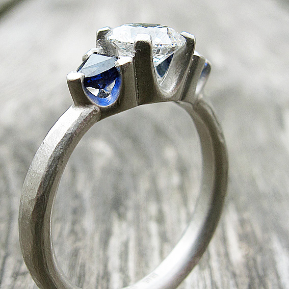 0.5 carat diamond, trillion blue sapphire and platinum engagement ring with an organic, hammered finish.