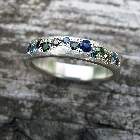 Pave set, white gold eternity ring with sapphires, tourmalines, cognac diamonds and topaz gemstones.