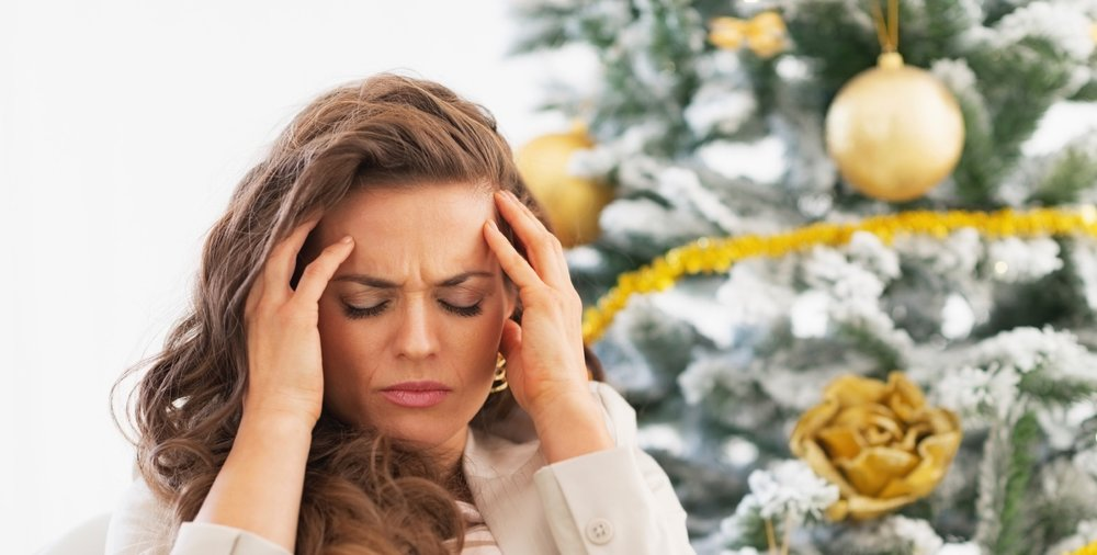 Portrait of frustrated young woman near christmas tree