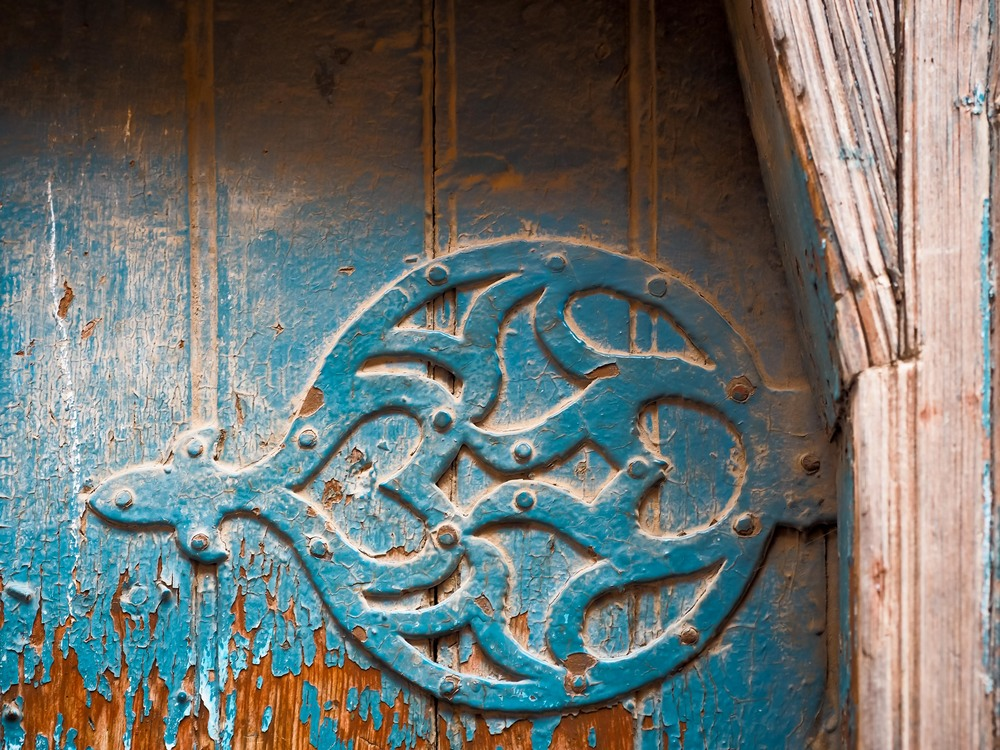 A detail of a painted blue metal hinge on a wooden door in Marrakech.