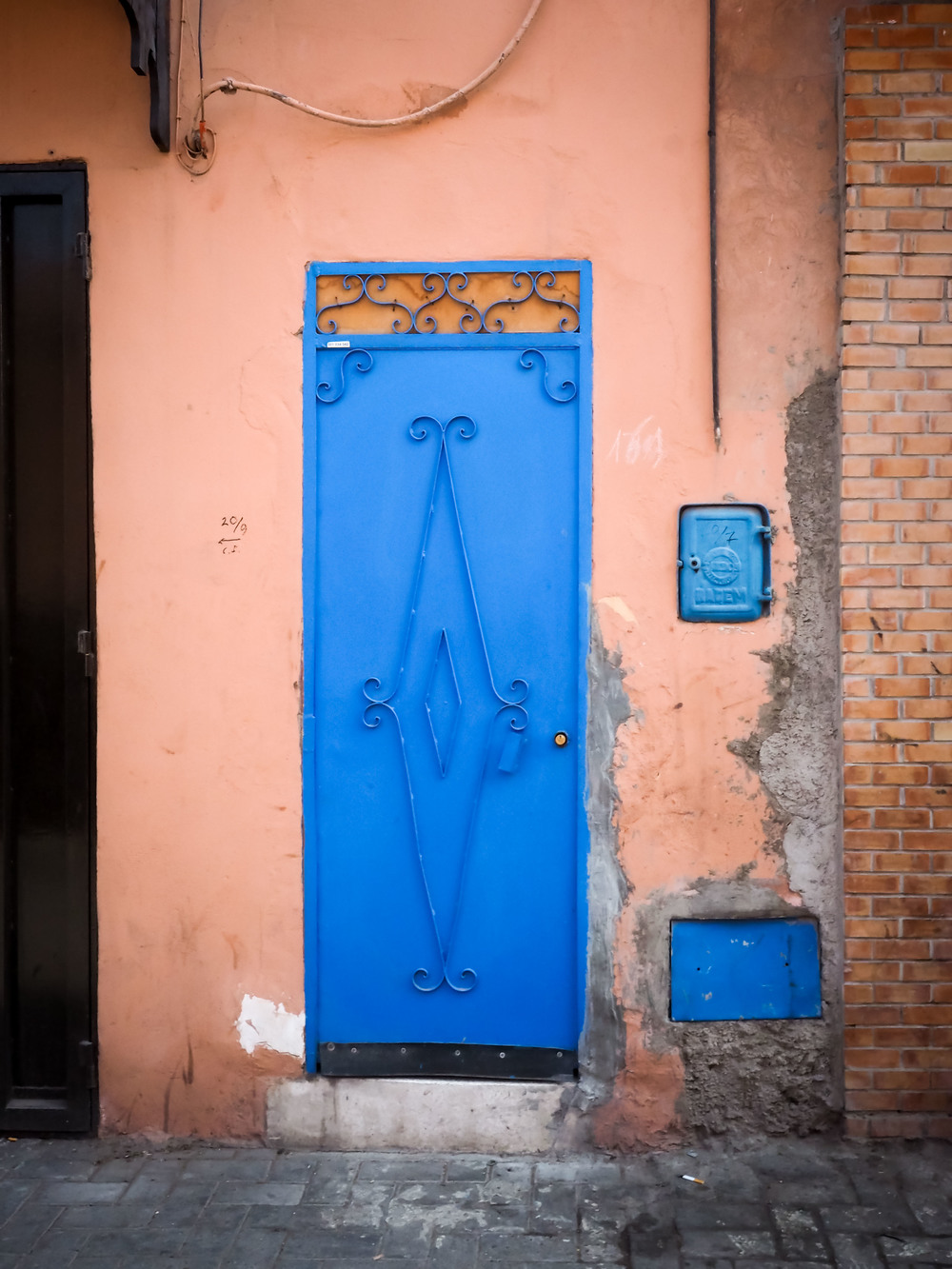 A bright blue metal door, with ornamental scrollwork.