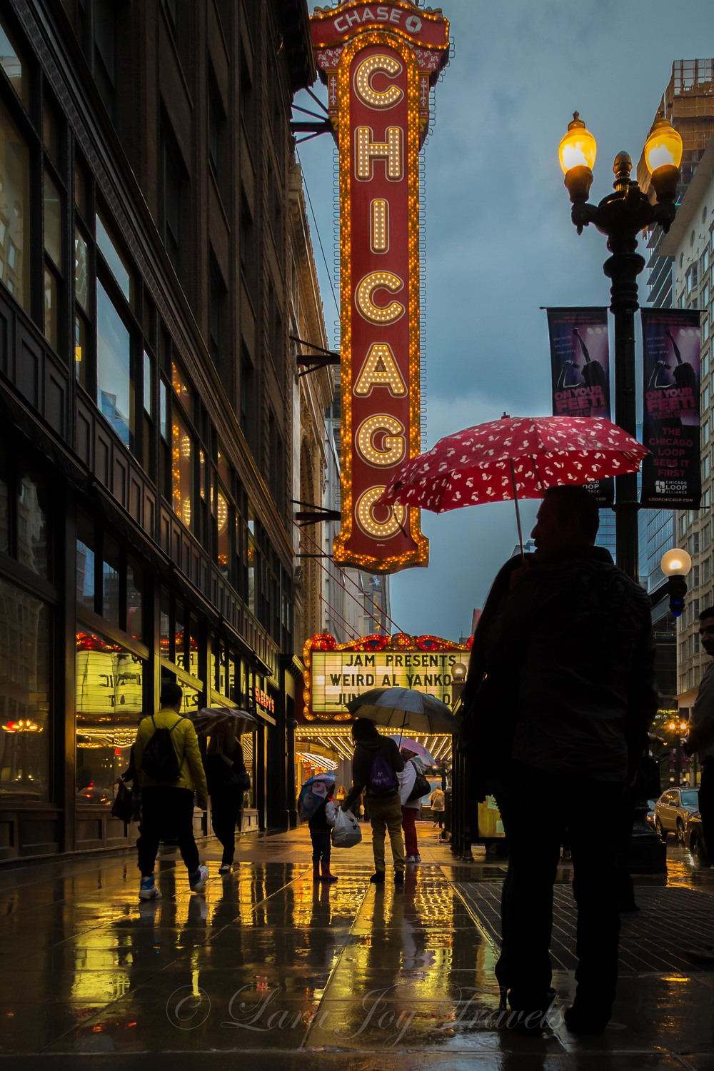Umbrellas, rain and the famed Chicago theatre sign.