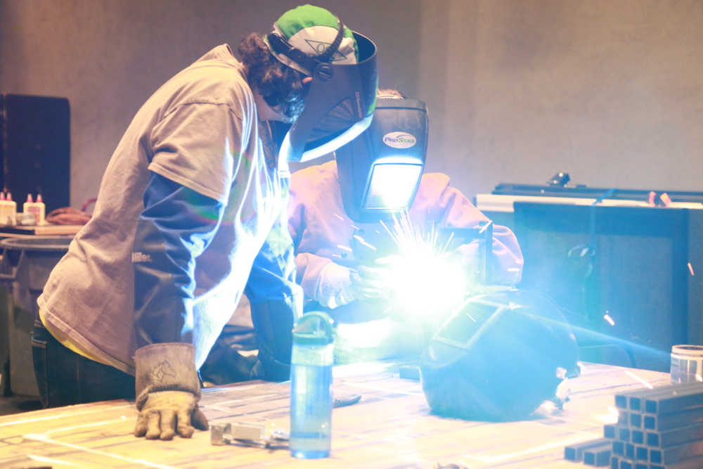 Guthrie Staff Carpenter Molly Diers observes as a Tech Tools participant welds. All our instructors are top-notch local professionals.  Photo Credit: Farrington Starnes