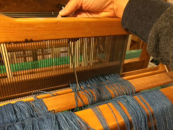 Pulling the warp threads through the reed.
